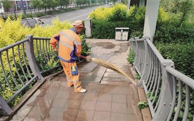 环卫工人清扫过街天桥上的雨水和落叶